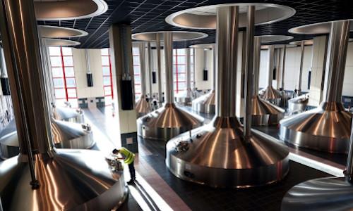 A worker inspecting vats at an Anheuser-Busch InBev brewery